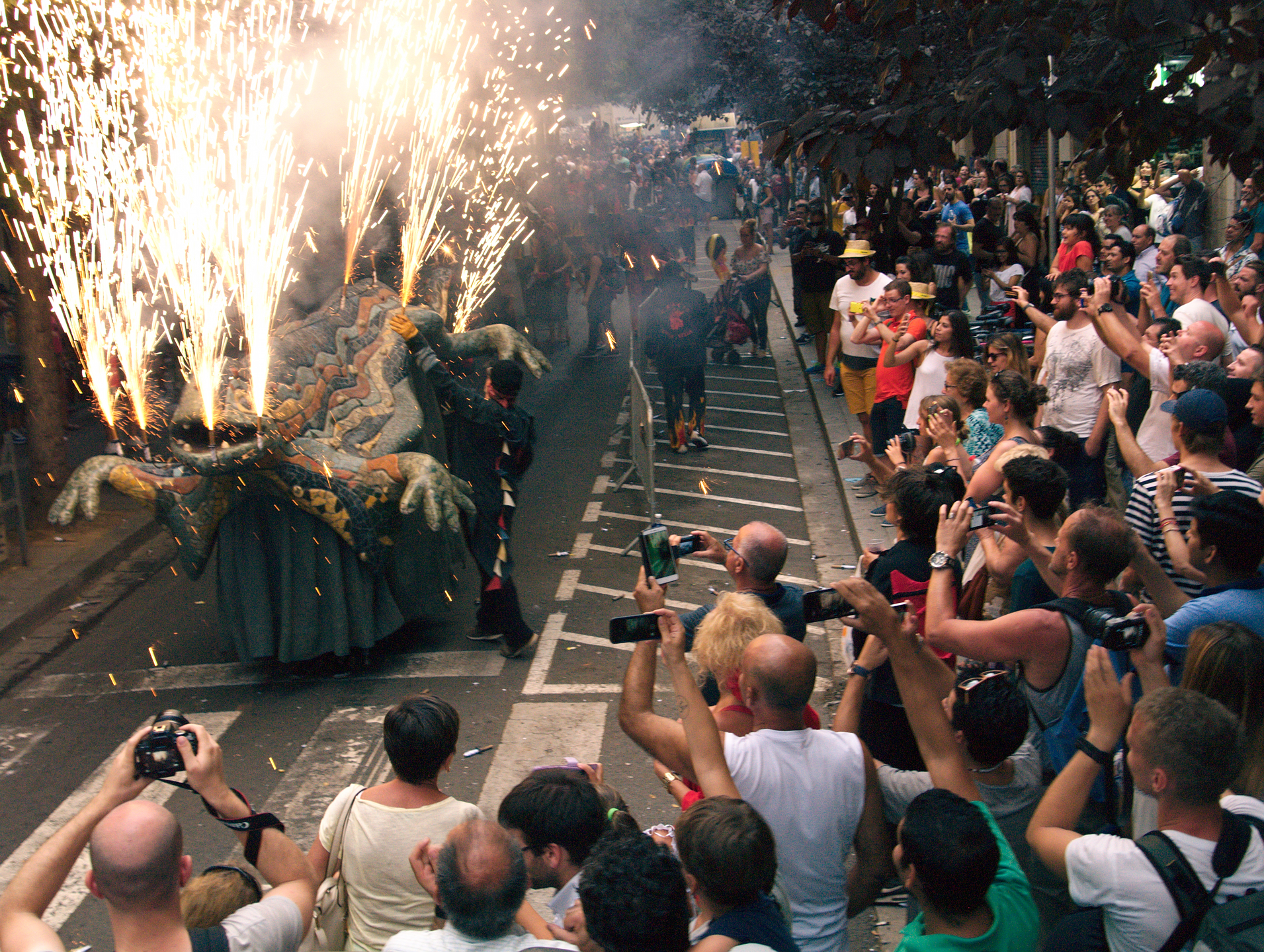 The Güell dragon replica with fireworks in C. del Torrent de l'Olla.